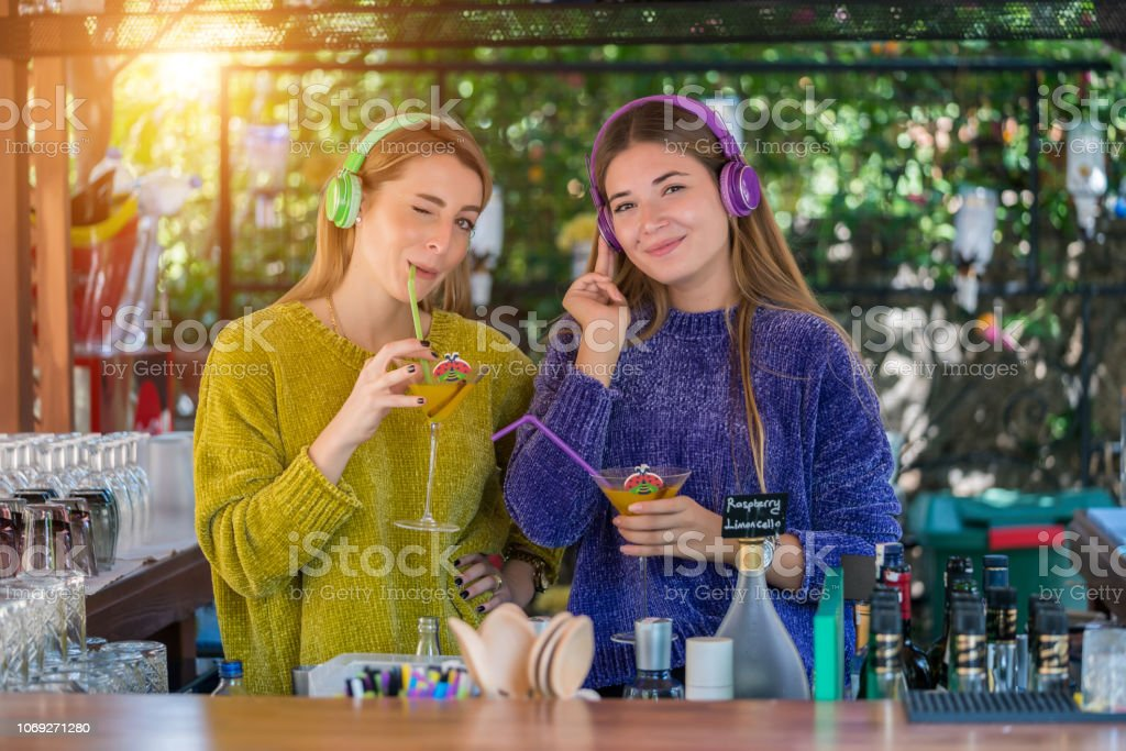 Pretty happy young women preparing cocktail and listening music at bar stock photo
