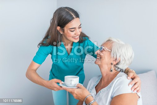 istock Pretty helpful carer talking with female patient 1011176586