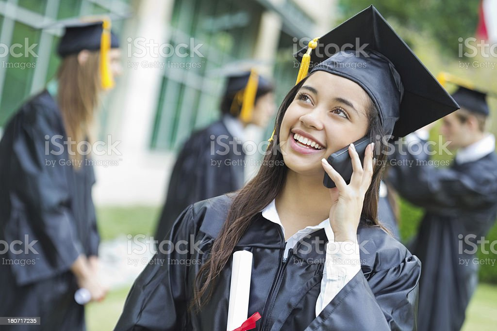 Pretty high school graduate calling someone after receiving her diploma royalty-free stock photo