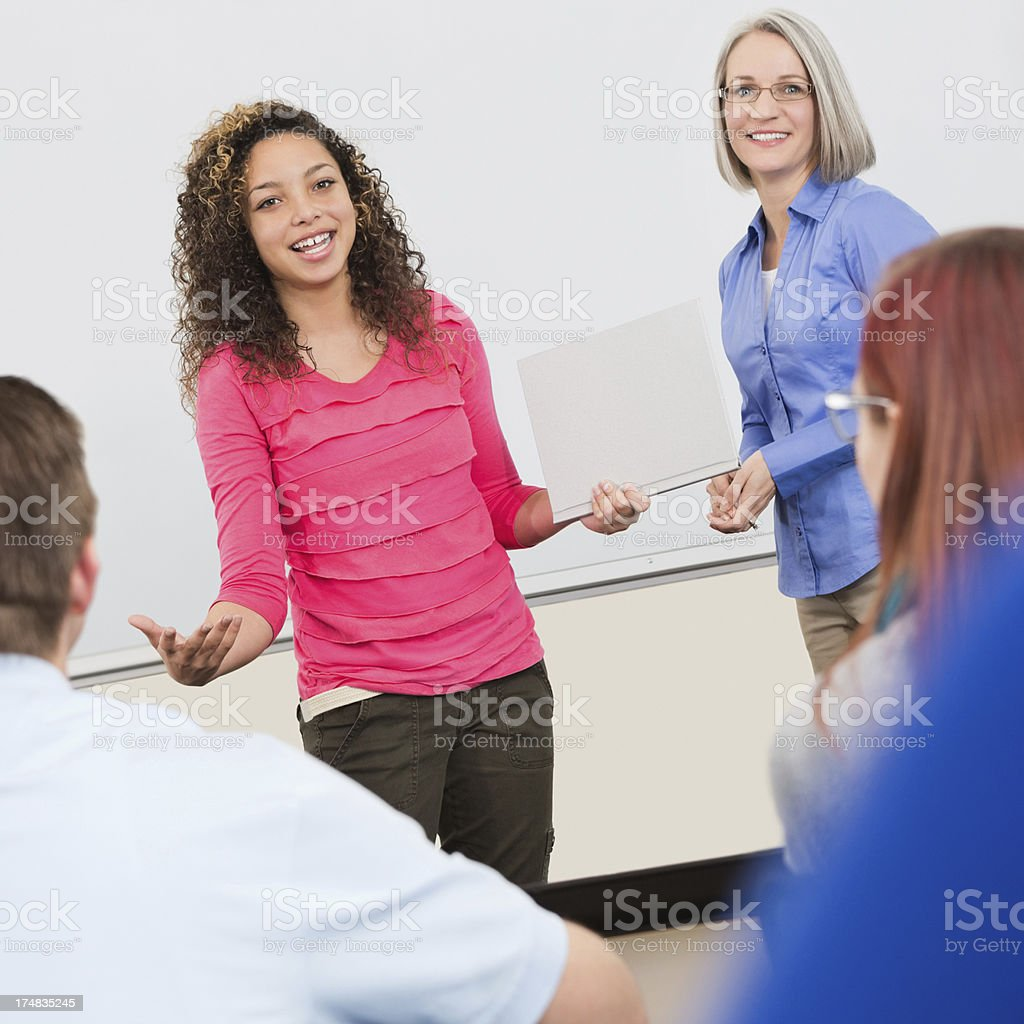 Pretty high school student giving presentation in class royalty-free stock photo