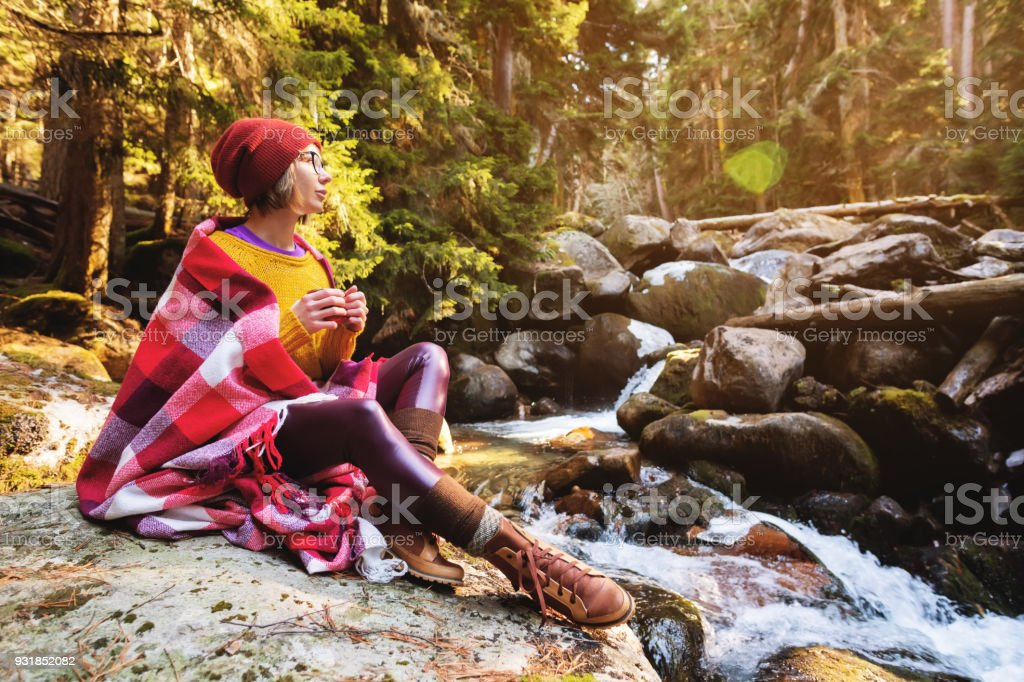 A pretty hipster girl with a plaid plaid on her shoulders in a hat and a yellow sweater and glasses with a mug of coffee in her hands looks at a mountain river sitting on a rock in a pine forest. The concept of freethinking travel around the world and the stock photo