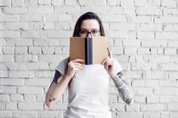 hübsche hipster tätowierte frau posiert in weißen t-shirt mit buch in händen, isoliert auf weißen mauer, ein buch in der hand halten, raum für design-layout - tattoos frauen arm stock-fotos und bilder