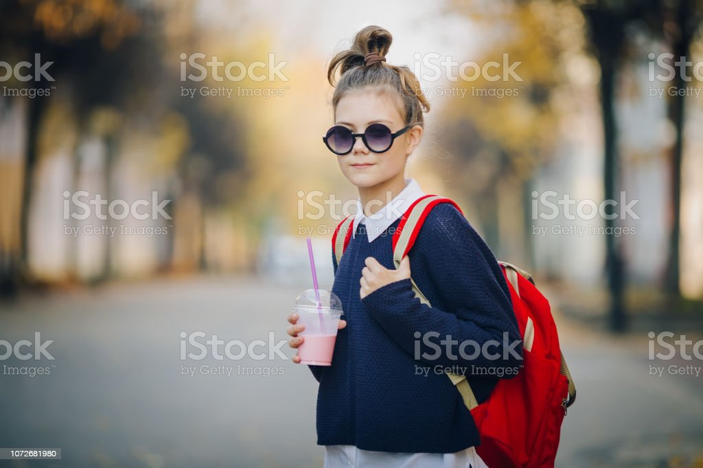 Pretty hipster teen with red bag drinks milkshake from a plastic cup walking street between buildings. Cute girl in sunglasses drinks a drink through a straw stock photo