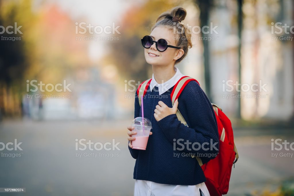 Pretty hipster teen with red bag drinks milkshake from a plastic cup walking street between buildings. Cute girl in sunglasses drinks a beverage through a straw stock photo
