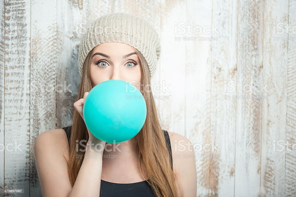 Pretty hipster woman is inflating colored balloon stock photo