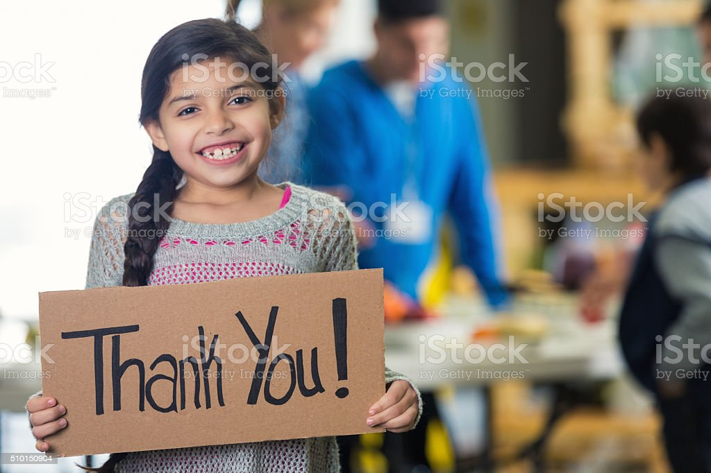 Pretty Hispanic girl holds 'Thank You!' sign in soup kitchen Cute Hispanic girl is holding a cardboard sign with 'Thank You!' witten on the board. She and her family are in a soup kitchen or food bank. She is smiling at the camera. Her brown hair is in a braid. Volunteers ar serving her family in the background. Focus is on the girl and the sign. A Helping Hand Stock Photo
