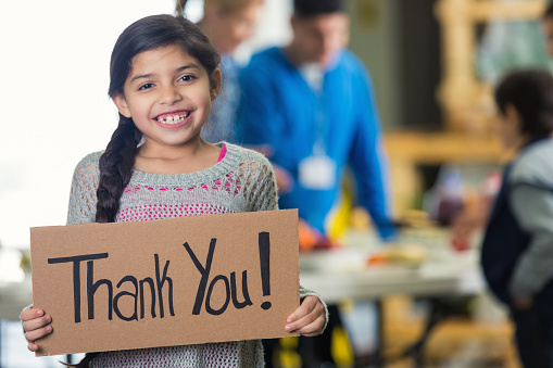 Pretty Hispanic Girl Holds Thank You Sign In Soup Kitchen Stock Photo - Download Image Now