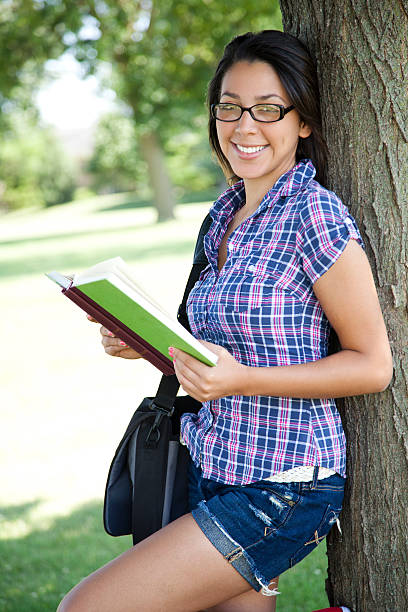 Pretty hispanic girl reading stock photo