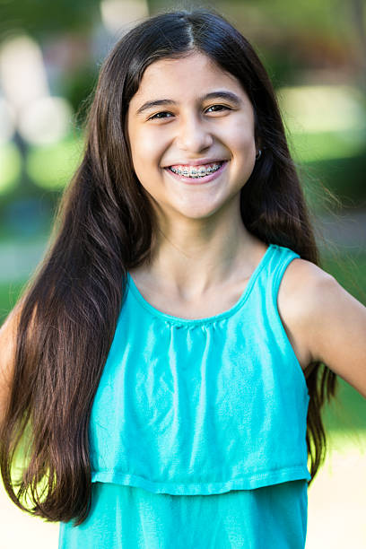 Pretty Hispanic preteen girl with braces, smiling at camera stock photo