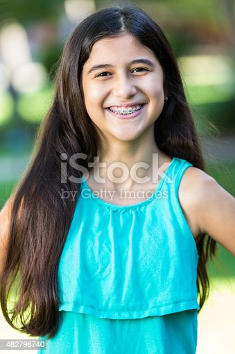 Pretty Hispanic Preteen Girl With Braces Smiling At Camera