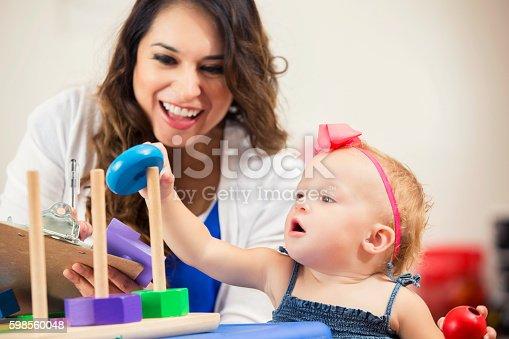 istock Pretty Hispanic teacher works with cute little preschooler 598560048