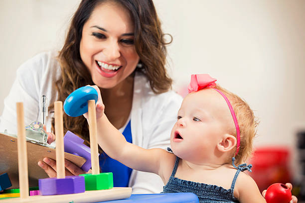 Pretty Hispanic teacher works with cute little preschooler stock photo