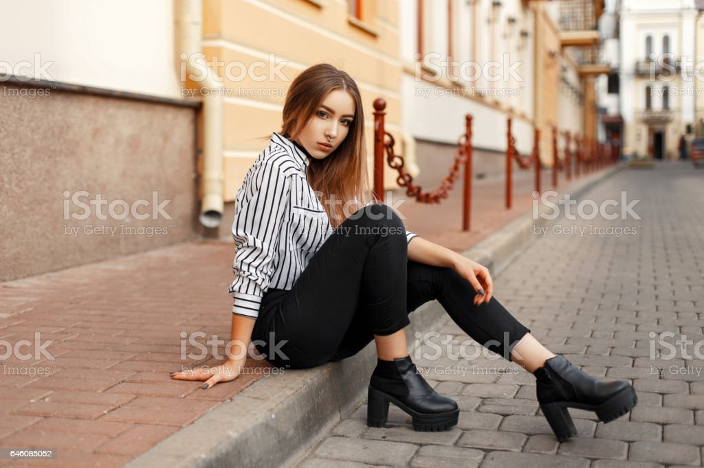 Pretty hot woman sitting on the curb. stock photo
