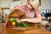 Attractive young woman with charming smile wearing apron standing at kitchen table and taking food out of grocery shopping bag, portrait shot
