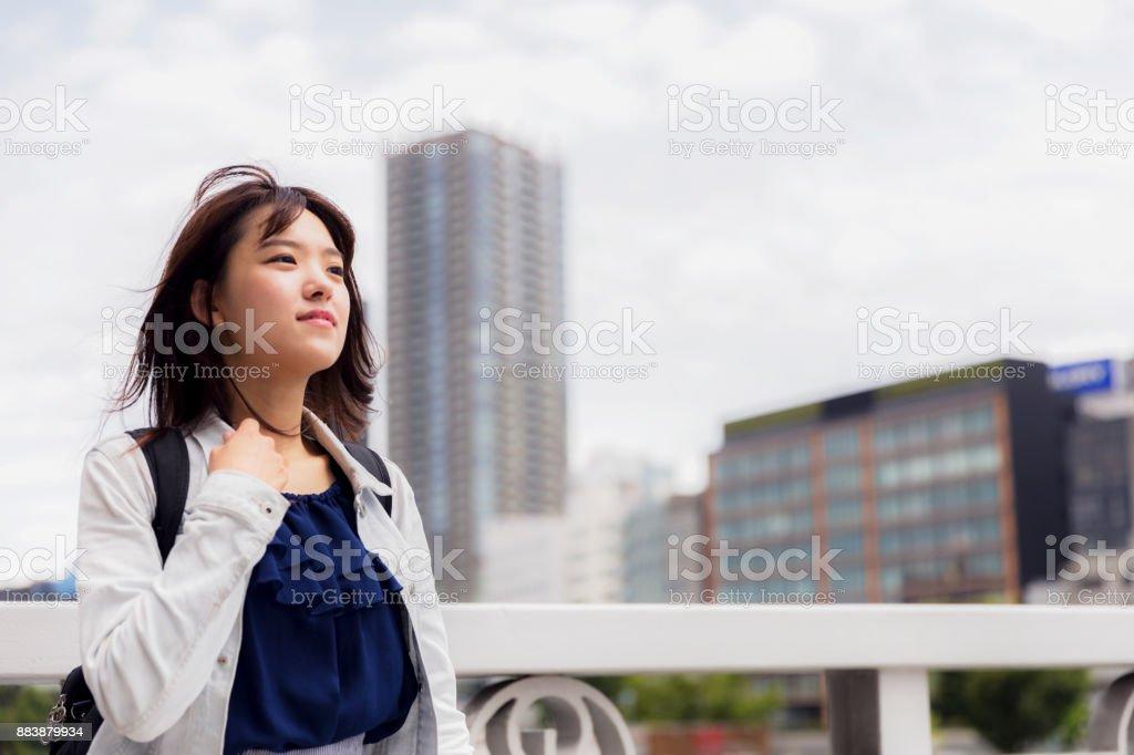 Menina bonita japonesa apreciando a brisa fresca em pé sobre uma ponte - foto de acervo