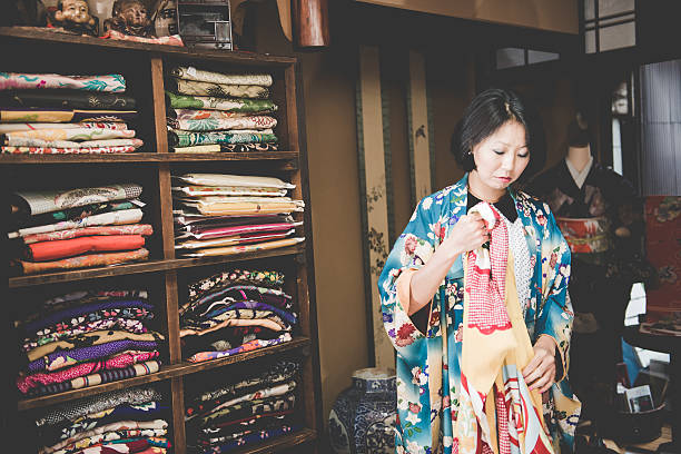 pretty japanese woman choosing yellow kimono in kyoto, japan - kimono stock-fotos und bilder