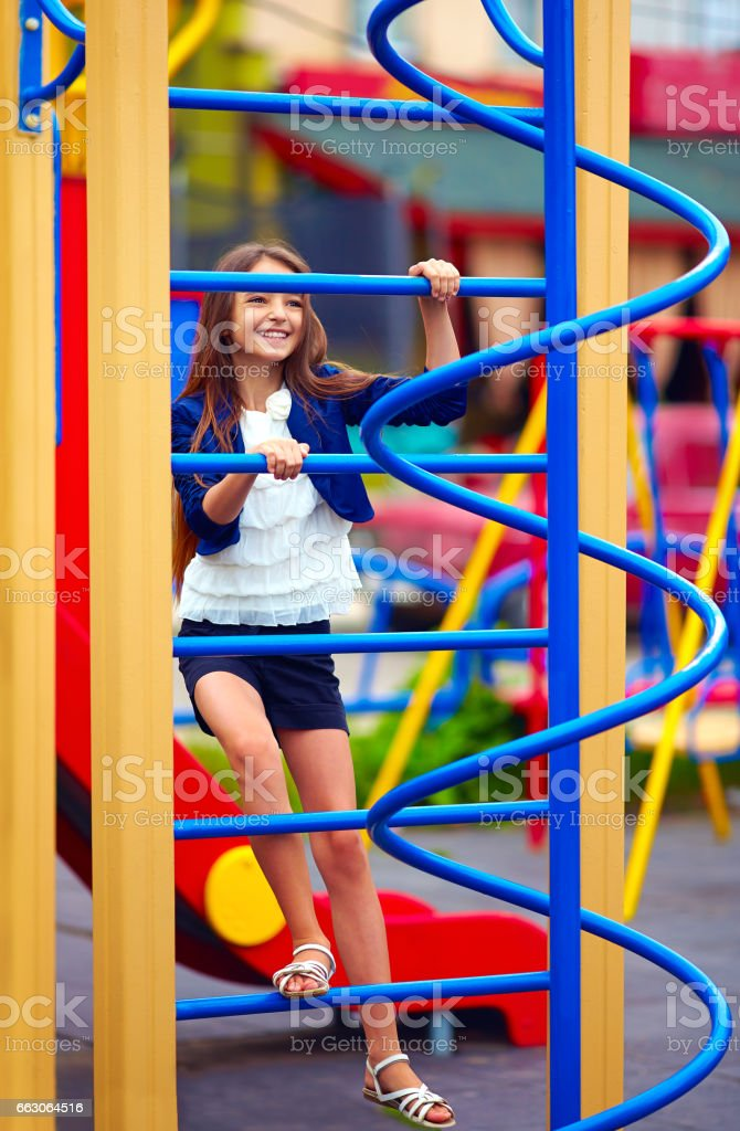 pretty kid, girl climbs on the stile at playground stock photo