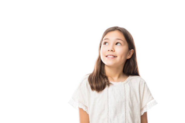 Pretty kid looking away isolated on white Portrait of a little schoolgirl looking away over white background 8 9 years stock pictures, royalty-free photos & images