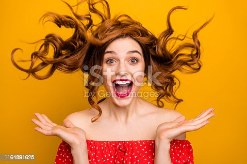 Pretty lady enjoy, warm spring breeze making curly hairstyle flight wear red dress isolated yellow background