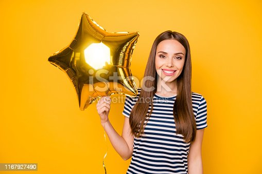 1035636416 istock photo Pretty lady holding hand star shaped air ballon wear striped white blue dress isolated yellow background 1167927490