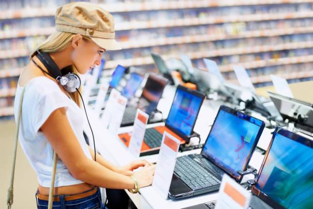 hübsche frau im einzelhandel computer store - freizeitelektronik stock-fotos und bilder