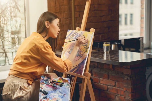 Pretty lady painting beautiful picture on easel at home stock photo
