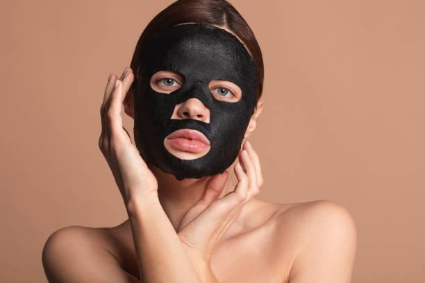 pretty lady touching her face while having black mask on it - sheet imagens e fotografias de stock