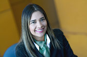 Pretty latin american receptionist working at a hotel looking at camera smiling