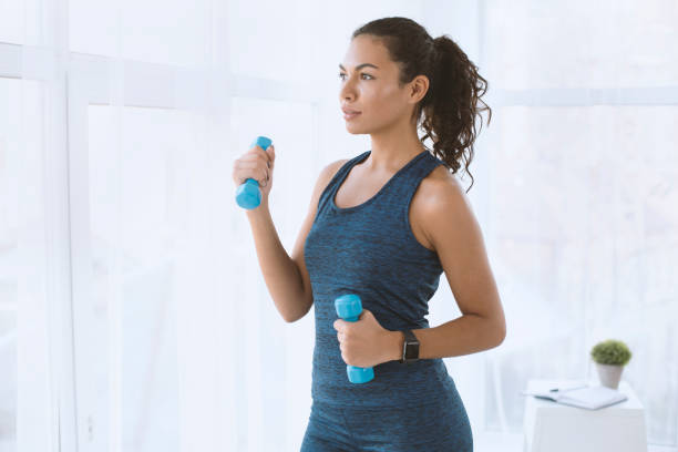 Pretty Latin woman working out with dumbbells at home, empty space stock photo