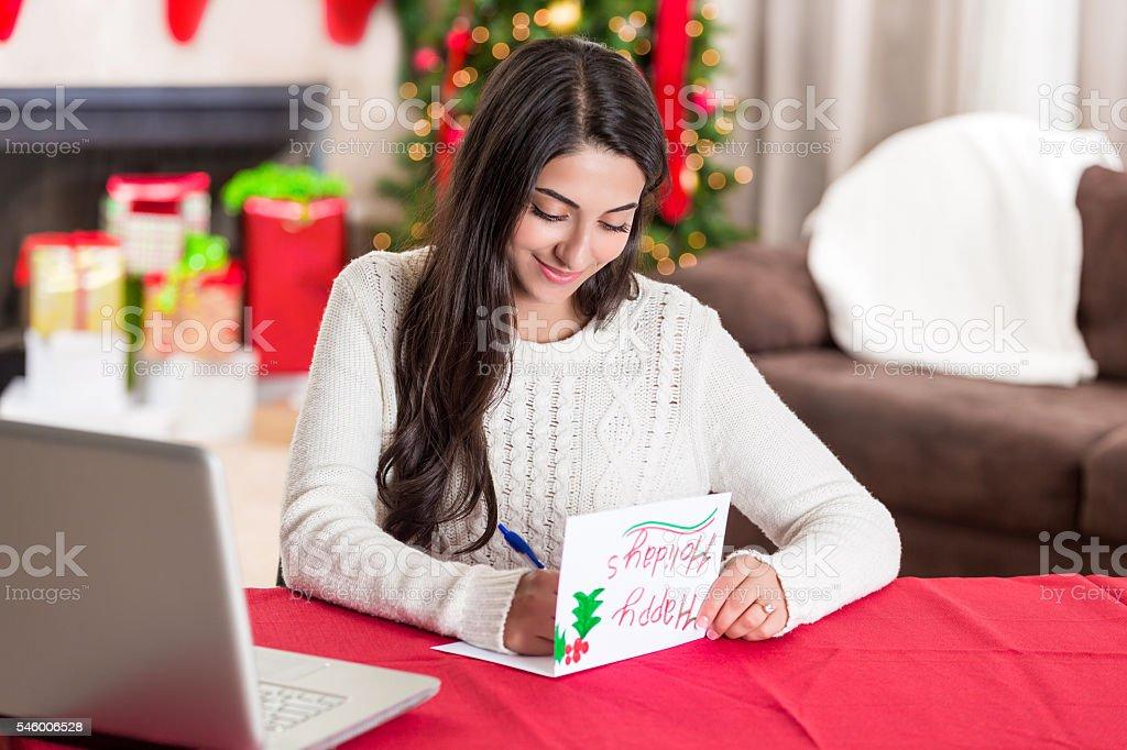 Beautiful Lebanese American Woman writing a christmas card during the...