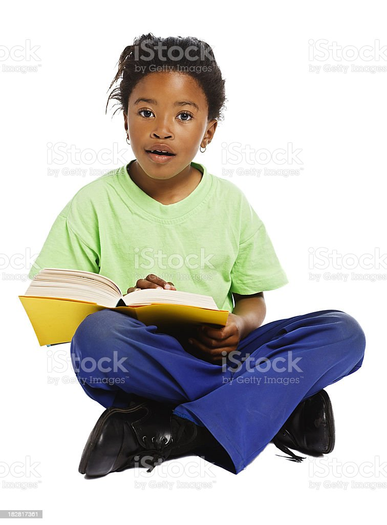 Pretty little African girl looks up from book she's reading royalty-free stock photo