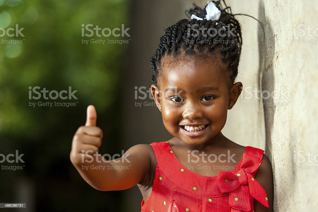 Pretty little african girl showing thumbs up. stock photo