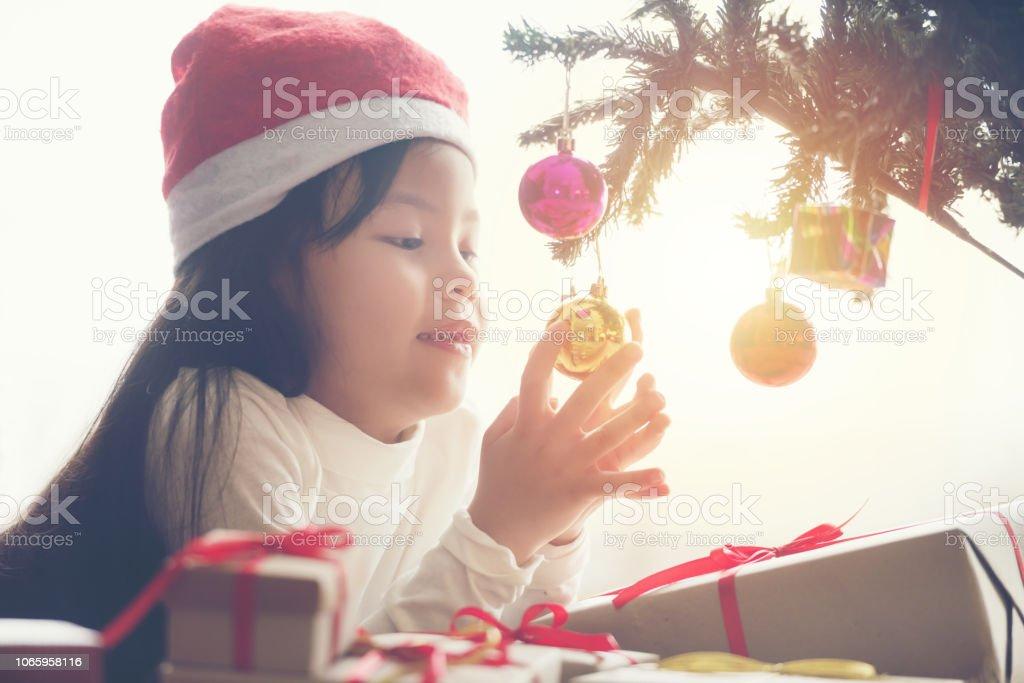 Pretty little asia girl happy and smile in santa cap white shirt near...