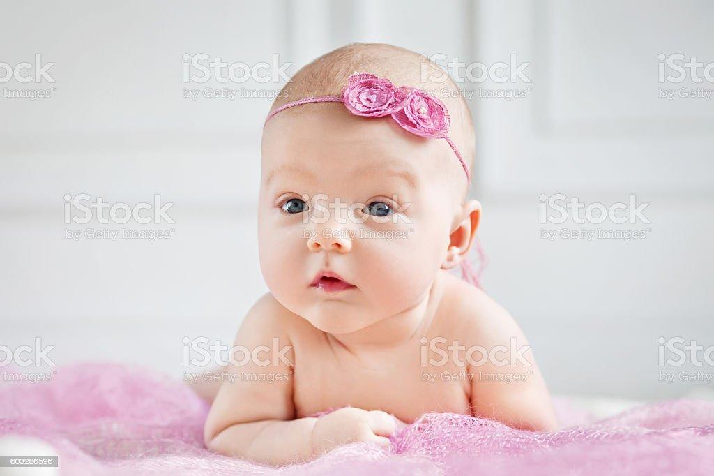 Pretty little baby girl lies on a stomach - foto de acervo