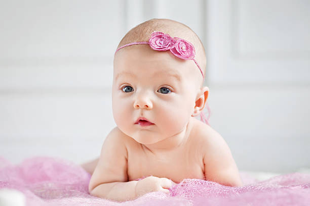 Pretty little baby girl lies on a stomach stock photo