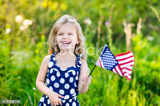 514069232 istock photo Pretty little blond girl holding an american flag and laughing 479138742