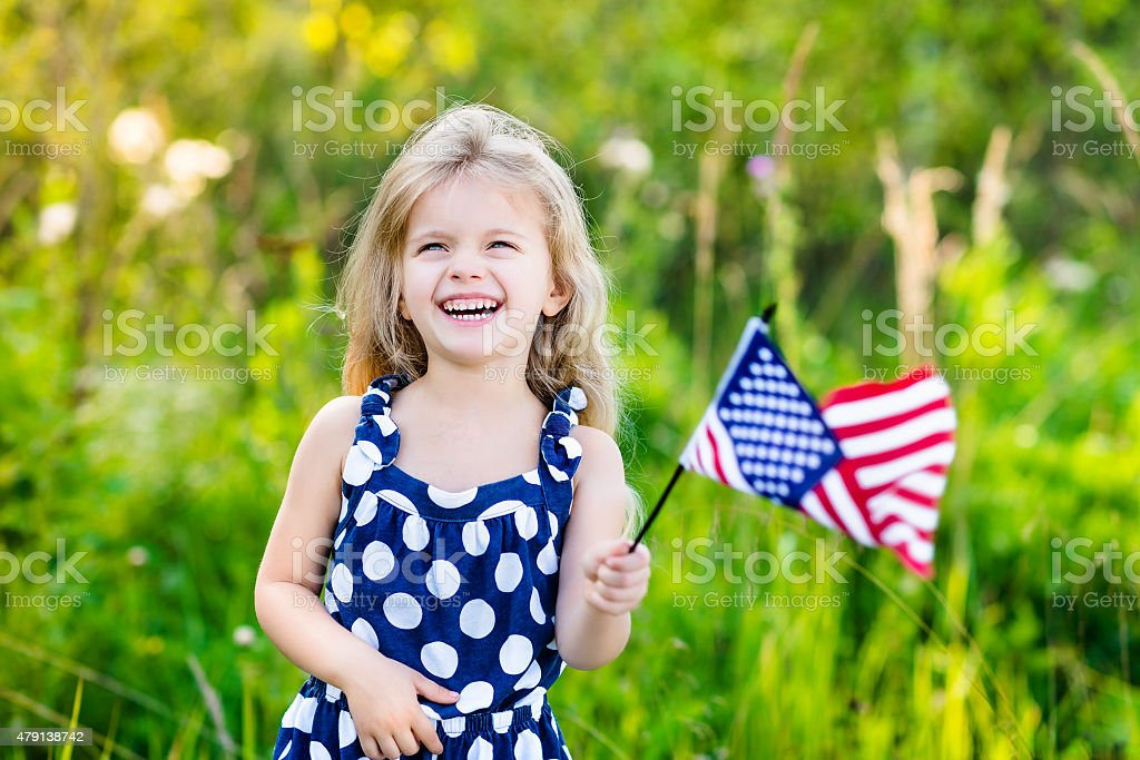 Pretty little blond girl holding an american flag and laughing stock photo