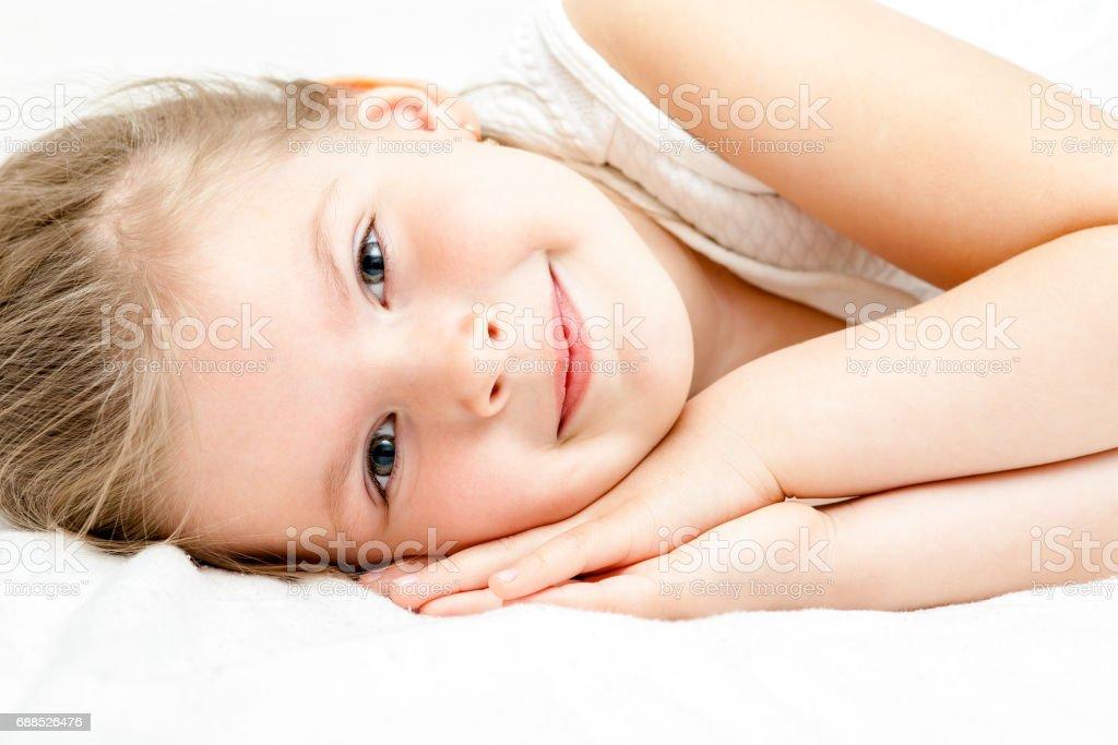 30506486b Pretty Little Blonde Girl Summer White Dress Lying On The Floor And ...