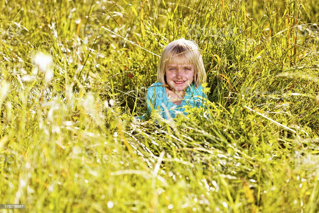 Pretty little girl almost concealed by grass in meadow stock photo