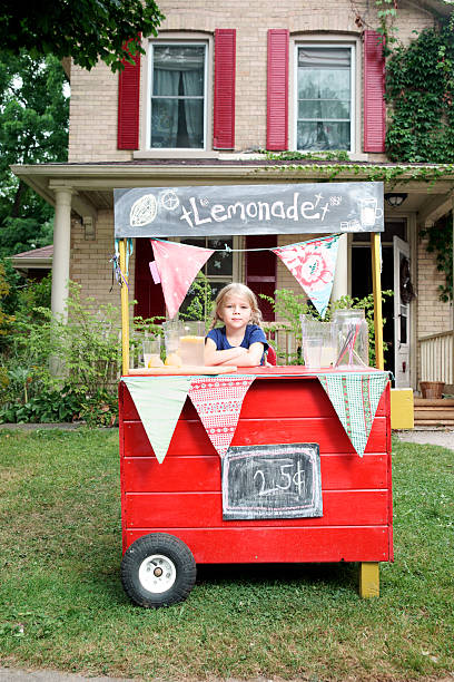 Pretty little girl and her lemonade stand.  lemonade stand stock pictures, royalty-free photos & images