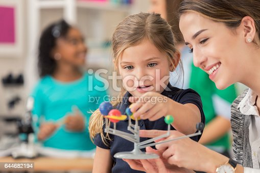 istock Pretty little girl asks questions about solar system 644682194