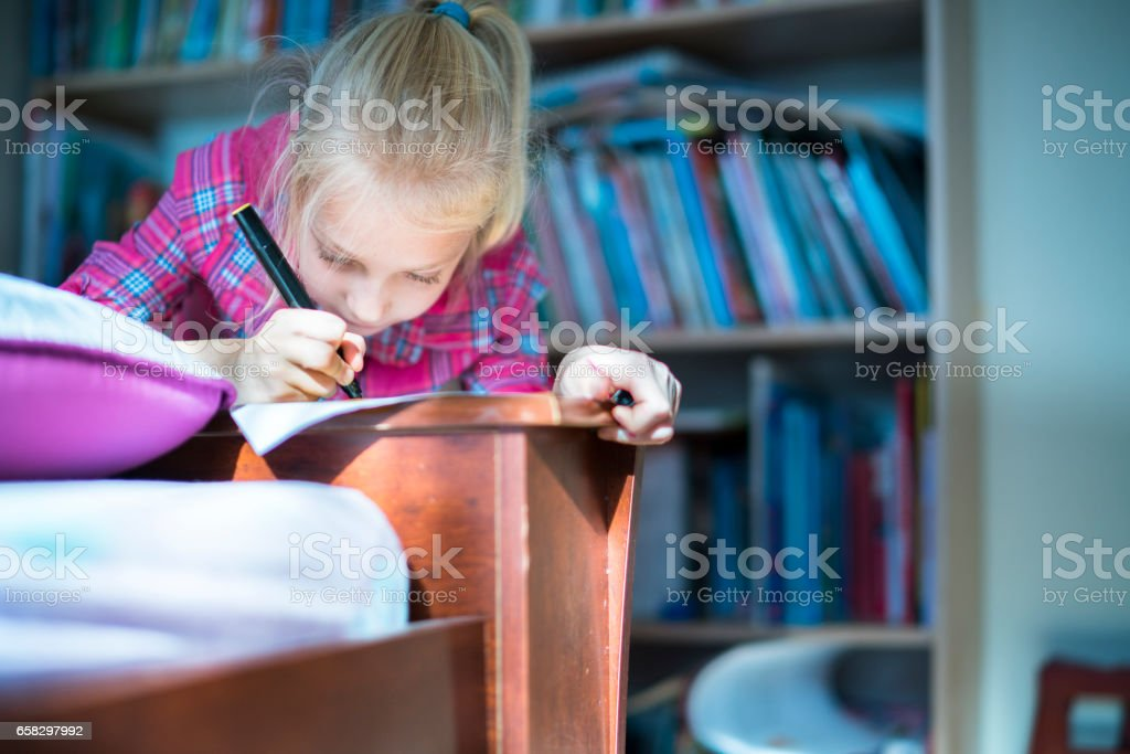Pretty little girl do homework in the kids room stock photo