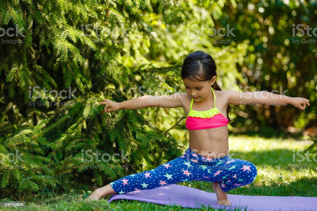 Pretty little girl doing exercises in the summer park stock photo