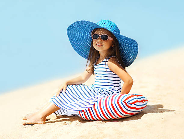Pretty little girl in a striped dress and hat stock photo