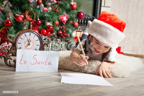 1062609644istockphoto Pretty little girl in christmas hat writes letter to Santa 453304023