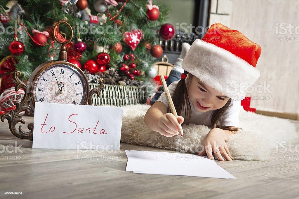 Pretty little girl in christmas hat writes letter to Santa stock photo