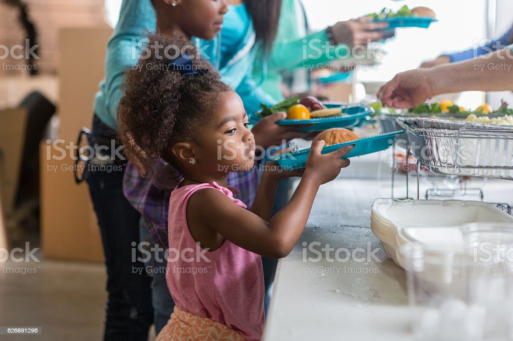 Pretty little girl in line at soup kitchen stock photo