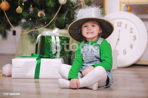 Pretty little girl in shine hat smiling with present near the Christmas tree.