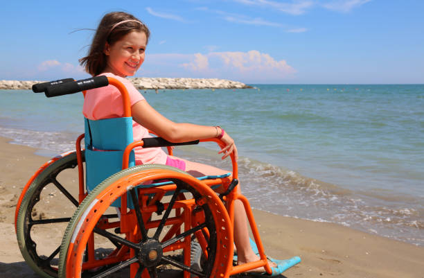 pretty little girl in the wheelchair by the sea - inpatient stock pictures, royalty-free photos & images