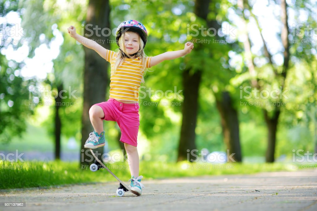 Linda menina aprendendo a andar de skate em lindo dia de verão em um parque - foto de acervo
